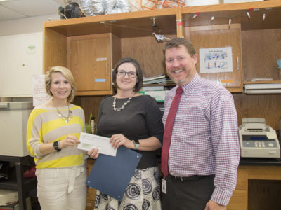TRTA Associate Director Cindee Sharp presents the grant to Bowie High School teacher Denise Sanders while Principal Mark Robinson looks on.