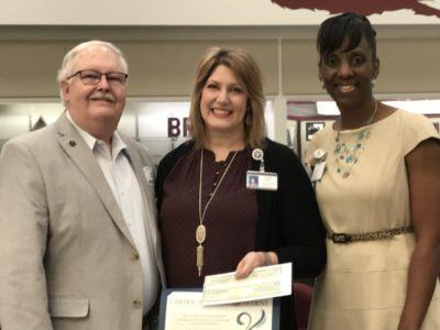 TRTF Board of Trustees President Jamie Larson delivers a classroom assistance grant to teacher Sara Willis, while Texas A&M Consolidated High School Principal Gwen Elder looks on.